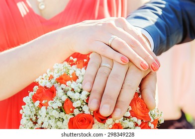 Groom and bride hands and rings on wedding bouquet