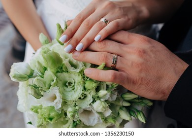 Groom and bride having wedding rings on their hands and touching above a beautiful bouquet. Bouquet is made of green, white buds of Eustoma Lisianthus natural flowers.