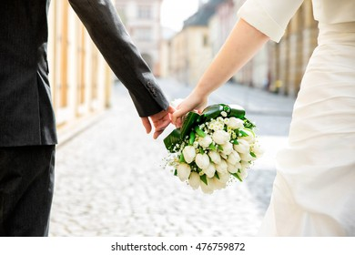 Groom with the bride holding a bouquet