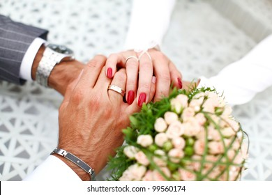 Groom and bride are holding hand of each other with feelings of love. Luxury decoration like a bouquet from roses, golden wedding rings and beautiful manicure.