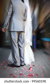 Groom and bride are holding hand of each other with feelings of love. Confetti from colorful petals are lying at the ground.