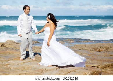 groom and bride holding hands on beach rocks