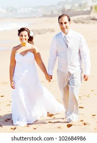 groom and bride holding hands walking on beach