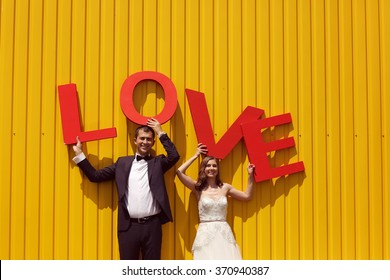 groom and bride holding LOVE letters
