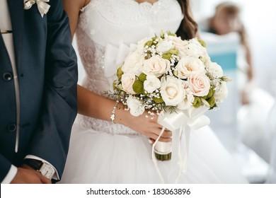 Groom and bride holding wedding bouquet on wedding ceremony
