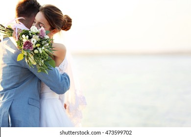Groom and bride hugging, outdoor