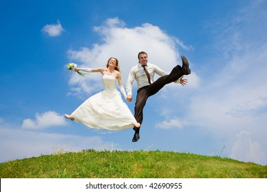 Groom and bride jumping against backdrop a sky and trees. In all growth.