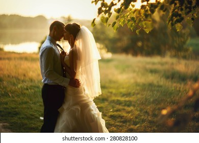 groom and bride is kissing on the background lake and forest