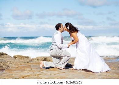groom and bride kissing on beach rocks