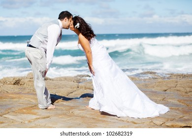 groom and bride kissing on beach