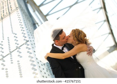 groom and bride kissing on a metal bridge