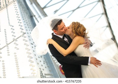 groom and bride kissing on a metal bridge
