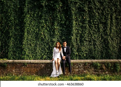 Groom and bride with naked legs sit on the brick wall