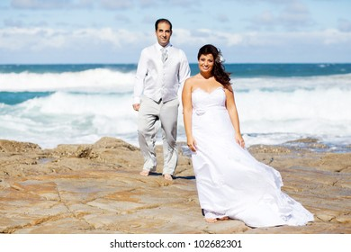 groom and bride on beach rocks