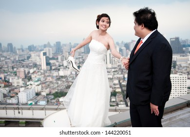 Groom and Bride on roof top building. wedding dress. Bridal wedding