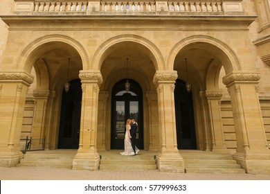 Groom and bride on stairs of a old building with columns
