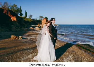 The groom and bride on a walk outdoors at the sea