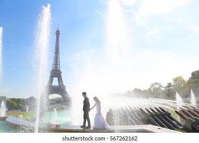 groom and bride in Paris near a splashing fountain