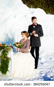 the groom with the bride pose near a holiday table with cake in the winter against an ice floe
