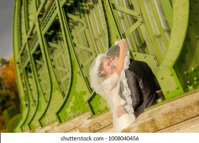 groom and bride posing in front of green structure