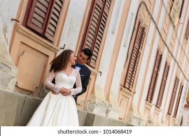 groom and bride posing near old house windows