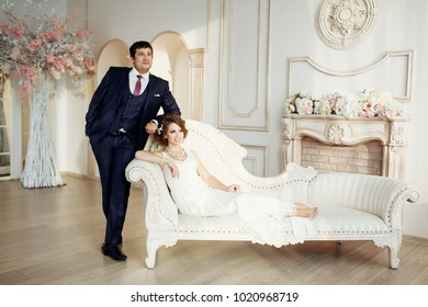 Groom and bride posing and smiling in studio for wedding shot. Wedding. Wedding day. Beautiful bride and elegant groom after wedding ceremony.