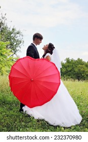 groom and bride with a red umbrella in the form of heart