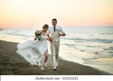 Groom and bride run along the shore against the wind