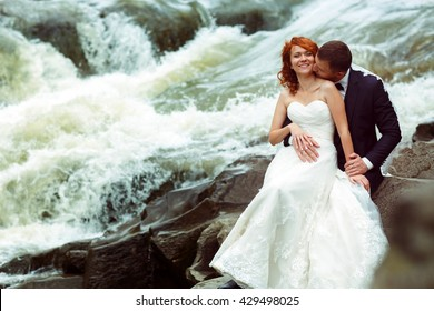 Groom and bride sit on the stones behind a foaming mountain river