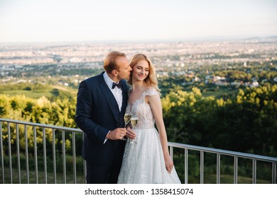 Groom and bride stand on the background of the city and drink champagne from wineglass. Clink glasses