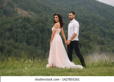 Groom and bride walkin thougt the carpatian mountains