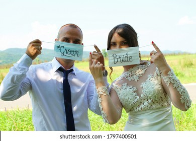 Groom and Bride wear/show medical face masks with the inscription 'groom' and 'bride' on their wedding day in nature during the COVID-19 virus. Photo shooting wedding day during the Coronavirus.