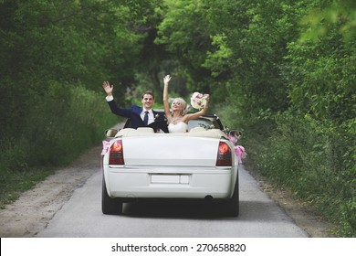 The groom and the bride in a white convertible car