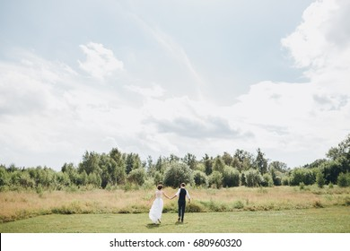 groom and bride in a white wedding dress are running across the green field against a forest background in a summer sunny day