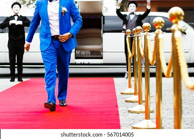 Groom in bright blue suit walks from white limousine on red carpet
