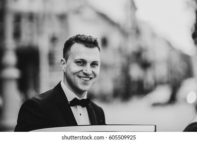 Groom with broad smile sits down in the car