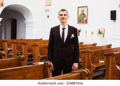 The groom in a brown suit in the church.