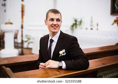 The groom in a brown suit in the church. Creative wedding photography.