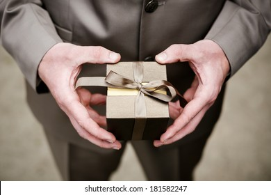 Groom in brown suit holding brown box (case) containing wedding rings