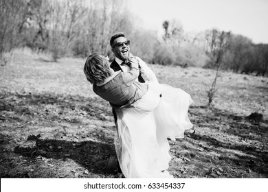 Groom carries bride in jeans jacket on the lawn