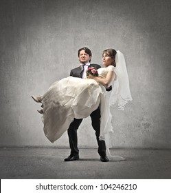 Groom carrying his wife in his arms