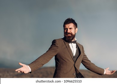 Groom in classic coat with bow tie on cloudy sky. Groom with beard and mustache on unshaven face wait outdoor.