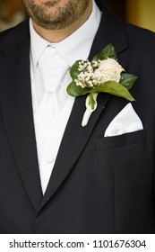 Groom clothes detail, bright white shirt and neck tie, black suit, white rose and lily of the valley