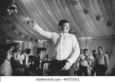 Groom dances with bride's garter in the middle of the dance floor