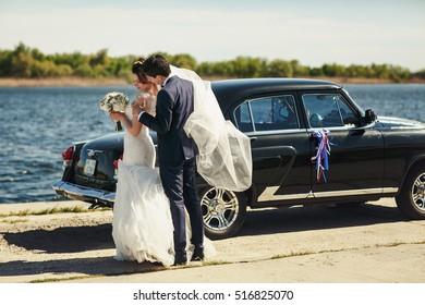 Groom in a dark violet suit holds bride's shoulders tender standing behind an old car