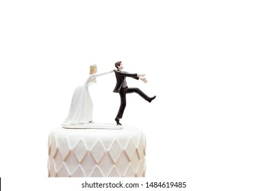 groom doll and statue is running away but bride can catch him finally. the funny wedding story doll on the top of cake with isolated object on white background and clipping path.