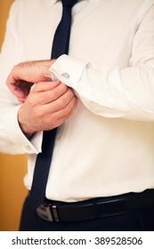 groom dresses cuff links on cuffs