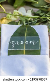 Groom Dried Leaf Table Card with Perspex Romantic Wedding Table Top Layout Table Spread no people no human tropical location with gold cutlery and scenic view