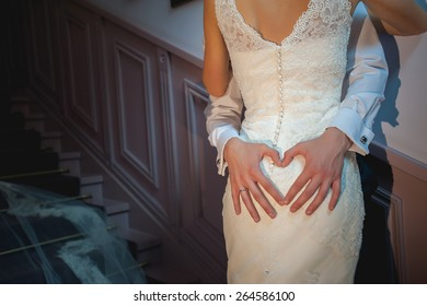 The groom embraces the bride and makes the heart of the fingers, concept, lifestyle, hipsters, wedding