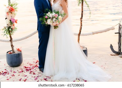 The groom embraces the bride on the beach. Wedding in Montenegro and Croatia.